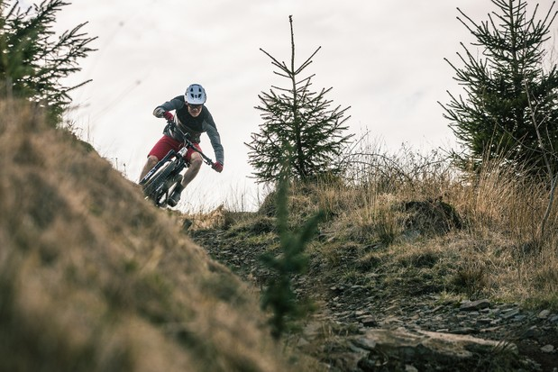Cycliste masculin en haut gris chevauchant le VTT tout suspendu Intense Primer 29 Expert en descente