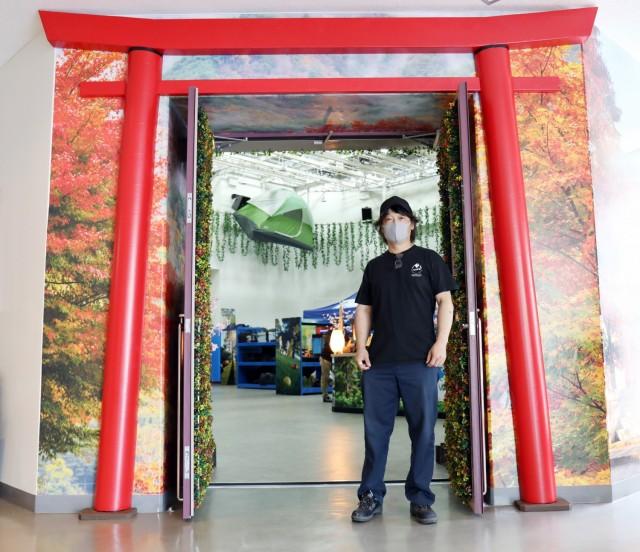 Kenji Osada, un employé de l'entretien de la famille et du moral, du bien-être et des loisirs du Camp Zama, se tient à côté de la porte torii qu'il a construite à la porte d'entrée de la nouvelle installation de loisirs de plein air, Camp Zama, Japon, le 30 avril. Osada a également construit un bâtiment de style japonais. pont et un affichage de pêche grandeur nature pour l'installation.