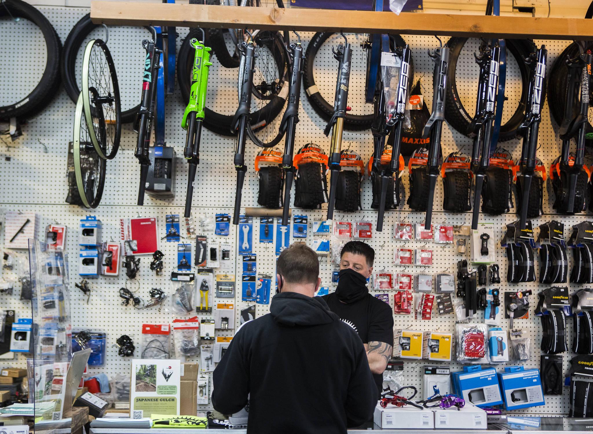 Jay Hiester, propriétaire de Tim ?? s Bike Shop, aide un client à choisir un pneu arrière vendredi à Everett.  (Olivia Vanni / Le héraut)