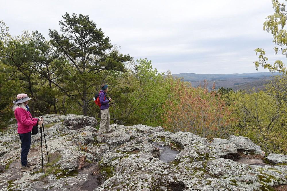 Carol Taylor (à gauche) et Karen Mowry admirent la forêt nationale d'Ozark lors d'une randonnée en avril 2021 dans la zone panoramique de Pedestal Rocks.  (NWA Democrat-Gazette / Flip Putthoff)
